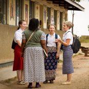 Kolme vapaaehtoista ja KUA:n työntekijä keskustelevat piirissä ugandalaisen koulun pihassa.
