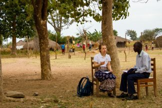 Suomalainen vapaaehtoinen keskustelee ugandalaisen opettajan kanssa. He istuvat puutuoleilla keskellä kenttää ja taustalla näkyy puita, rakennuksia ja lapsia.