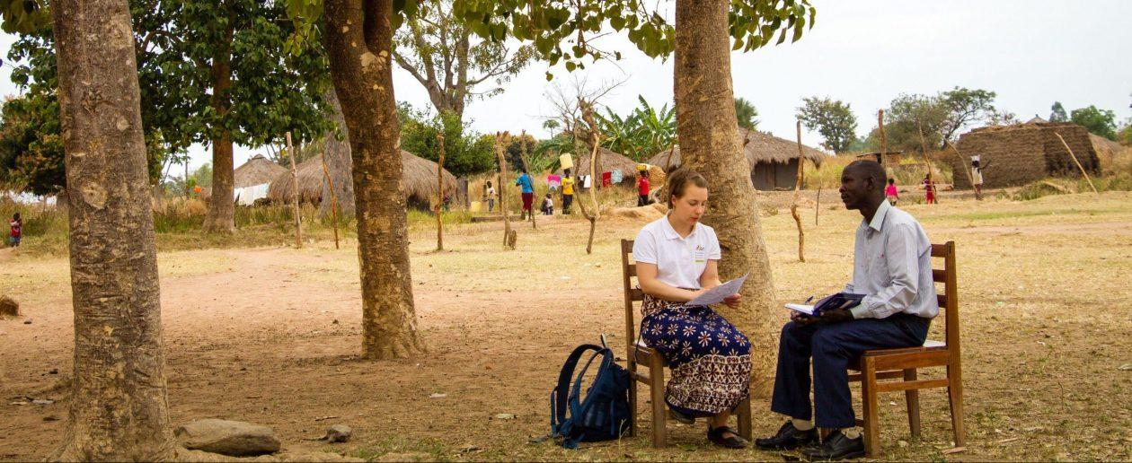 TwB volunteer Saara Turunen giving feedback after lesson observation to P6 teacher Onzima Sirati Sebbi outside Bamure Primary School in Koboko.