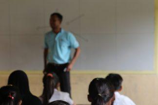 Opettaja puhuu luokan edessä.