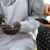 Vapaaehtoinen ja paikallinen kollega näpyttelevät puhelimiaan.