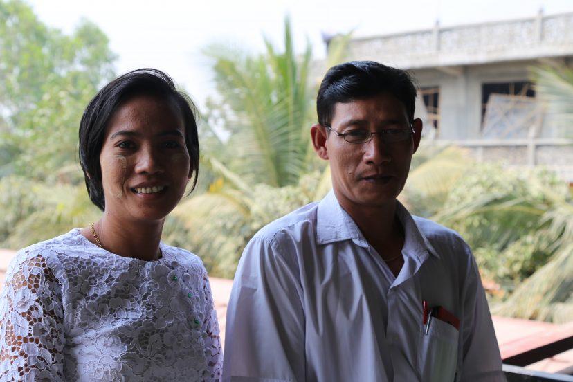 Kaksi opoa Myanmarista valkoisissa paidoissa katsoo kameraan.