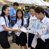 Hymyilevä nainen ojentaa esitteen kolmelle tytölle opo-messuilla Kamdodzassa.