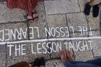 Neljän ihmisen jalat näkyvät tekstin vieressä, joka on kirjoitettu maahan. Viivan toisella puolella lukee lessons learn ja toiselle puolella lessons taught.
