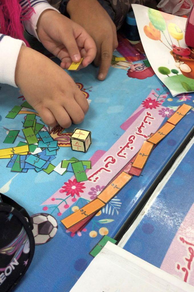 Lapsi järjestelee värikkäitä paperin paloja.