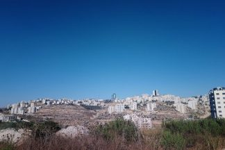 Kaupunkimaisema, jonka taustalla näkyy kirkkaan sininen taivas.