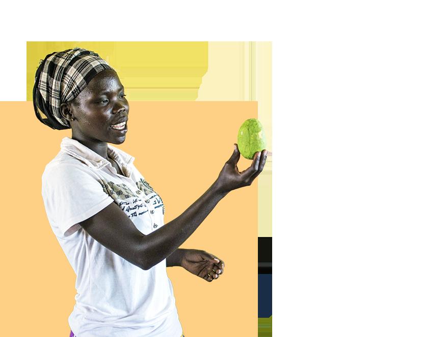 Ugandalainen nainen pitelee edessään hedelmää.