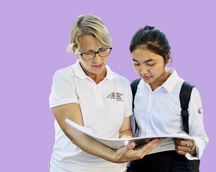 Suomalainen vapaaehtoinen ja kambodzalainen oppilas katsovat yhdessä edessä olevaa kirjaa. Vapaaehtoisella on paita, jossa on englannin kielinen Opettajat ilman rajoja -logo.