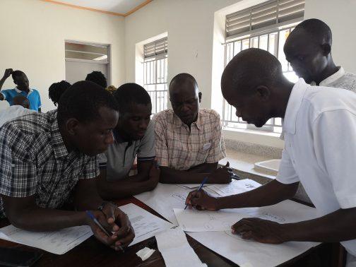 Neljä miestä kirjoittaa edessä olevaan paperiin.