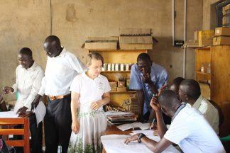 Joukko ugandalaisia miehiä keskustelee iso paperi edessään pöydällä. Vapaaehtoinen tarkastelee paperia.