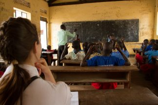 Vapaaehtoinen istuu ugandalaisen luokkahuoneen takaosassa ja seuraa opetusta.