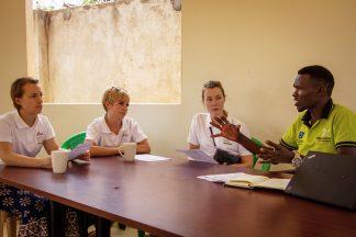 Ugandalainen työntekijä puhuu kolmen vapaaehtoisen kuunnellessa.