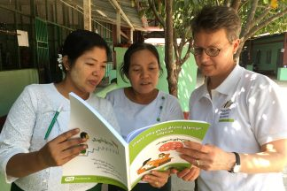 Vapaaehtoinen ja kaksi myanmarilaista naista tarkastelevat kirjaa.