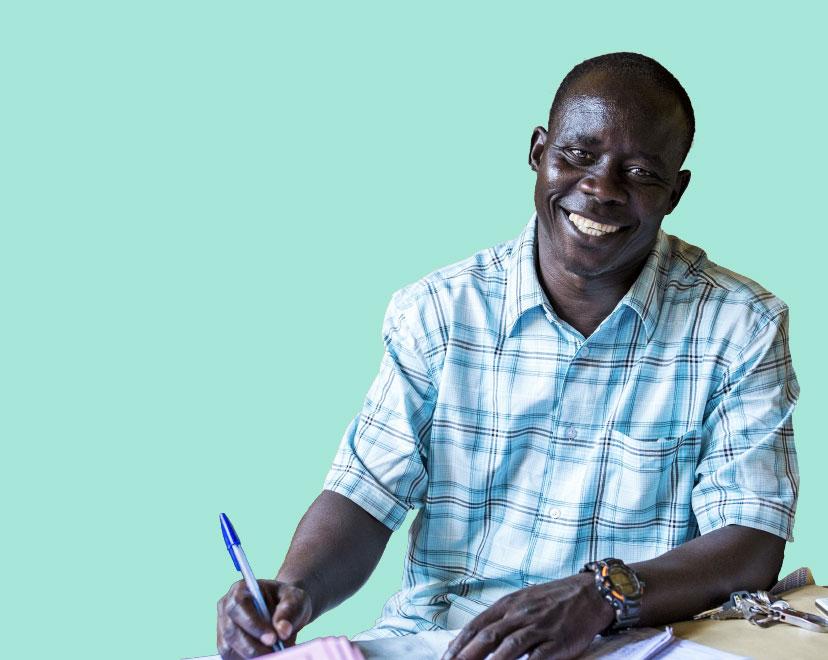 Ugandalainen mies katsoo kameraa ja hymyillee. Hänellä kädessään kynä ja edessään useita papereita.