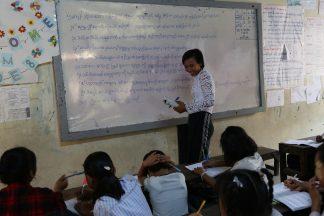 Opettaja hymyilee luokassa oppilaille