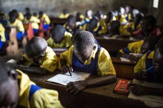 Lapset kirjoittavat vihkoisinsa luokkahuoneessa.