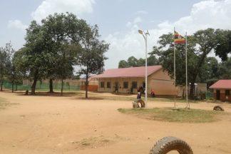 Hiekkakentän toisella laidalla on koulurakennus.