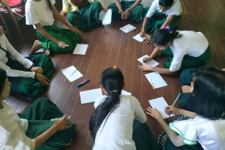 Students sit on floor in a ring with paper in front of them.