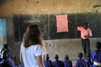 Vapaaehtoinen seisoo ugandalaisen luokkahuoneen taka-osassa ja seuraa opettajan opetusta.