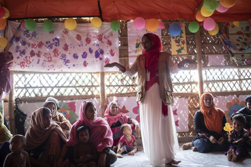 Nainen seisoo naisjoukon keskellä ja puhuu heille. Taustalla on ilmapalloja ja lasten piirustuksia.
