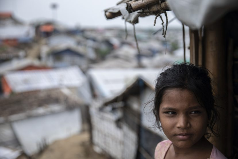 Tytön taustalla näkyy pakolaisleirin maisemaa.