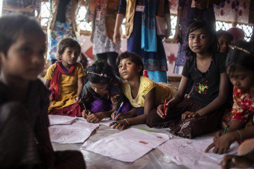 Lapset istuvat lattialla ja kirjoittavat.