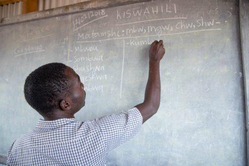 Opettaja kirjoittaa liitutaululle.