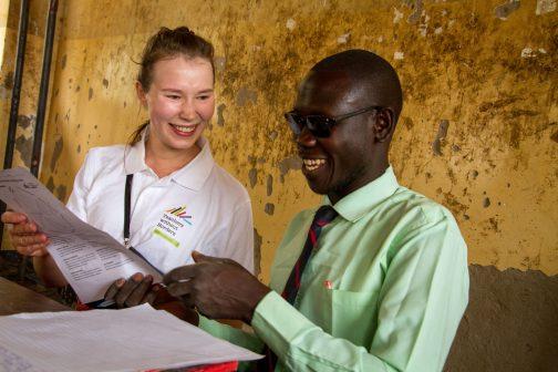 Vapaaehtoinen ja opettaja katsovat yhdessä nauraen edessä olevia papareita.