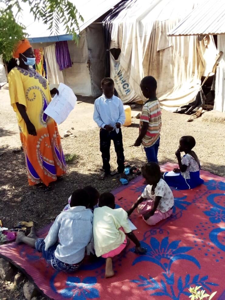 Opettaja neuvoo maski kasvoilla viltillä istuvia oppilaita.