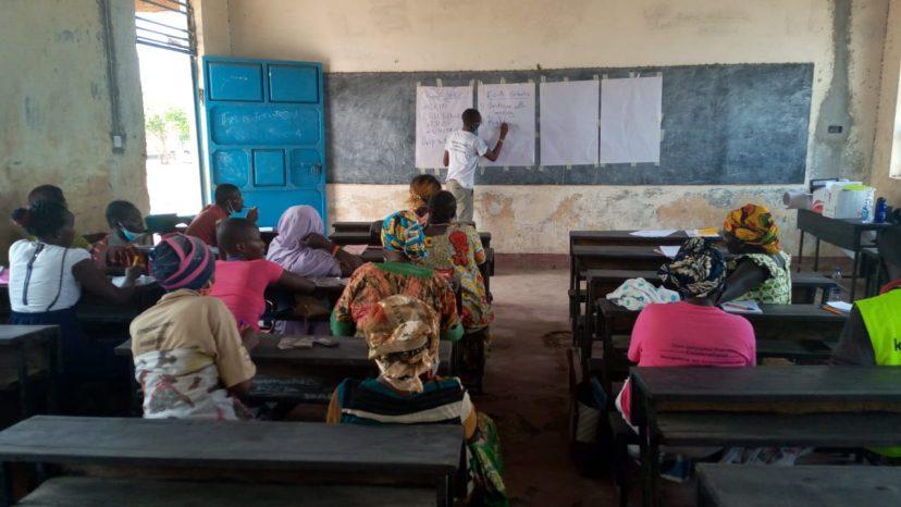 Oppijoiden vanhemmat istuvat luokassa ja kouluttaja kirjoittaa taululle.