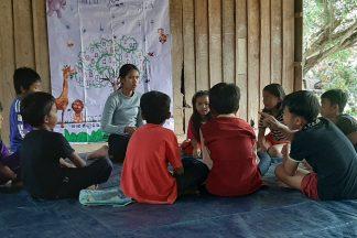Ohjaaja ja oppijat istuvat piirissä maassa. Taustalla on iso puun kuva.