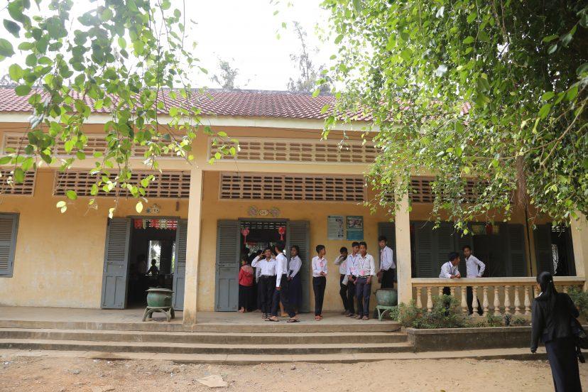 Koulurakennus, jossa oppilaita etualalla.