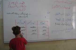 Oppija kirjoittaa luokan taululle.